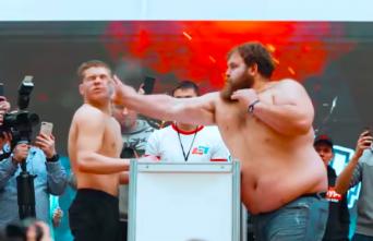 テーブルをはさんで男たちがビンタの張り合いで真っ向勝負。耐えて叩く、ロシアのビンタコンテスト