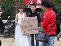 「妻を売って娘を助ける」と書いたダンボールを掲げる夫婦