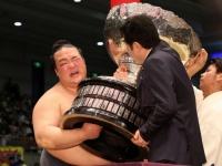 内閣総理大臣杯を受け取り顔をゆがめる稀勢の里(写真:日刊スポーツ/アフロ)