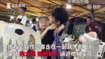 花束を手に、無理やり男性客に抱きつく少女(この件を伝えるニュース映像サイト「看看新聞」より)