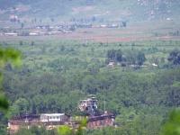 韓国軍施設(手前)と森を挟んで先にあるのが北朝鮮の監視所。奥には集落が広がっていた