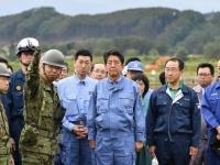 北海道胆振東部地震の被災地を訪問する安倍晋三首相(中央)(写真:毎日新聞社/アフロ)