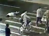 路上に倒れた女性の傍らを、多くの人がただ通り過ぎる