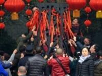 柱に群がるようにして、下から紅絲帯を引っ張る観光客たち