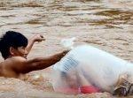 学校に通わせるため、子どもを袋に入れて濁流の川と闘う父親。