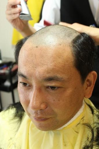男性用かつらを体験するために髪を剃る記者
