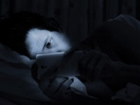 ベッドの中で片目でスマホを見続けると……(shutterstock.com)
