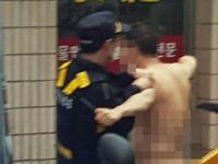 警察官に身柄を拘束される全裸男