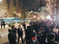 歩道に膨れあがるデモ参加者たちに対し、必死で鉄柵を押さえつける警官たち(3月30日撮影)
