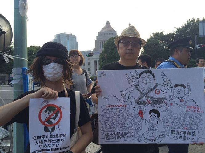 筆者が国会前デモしたときの様子(左が著者、右が中国人風刺漫画家の変態唐辛子さん)