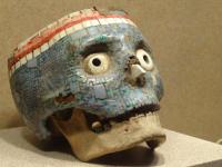 人間の頭蓋骨に宝石でモザイクが施されたアステカ族の宗教的装飾品