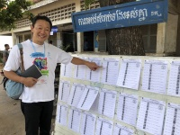 投票所に設置された顔写真付きの名簿を指さす、国際NGOインターバンド理事の阪口直人氏。水増し登録などの不正を防ぐため、選挙人登録は電子化された。(カンボジア総選挙当日の2018年7月29日、プノンペン市内の投票所にて撮影)