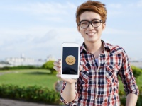 Vietnamese guy showing smiling emoji on the screen of his smartphone
